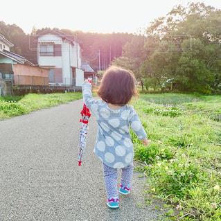 子ども,空,夕日,雨,傘,屋外,緑,夕焼け,夕暮れ,女の子,草,道,人,水玉,幼児,夕陽,雨上がり,梅雨,お散歩