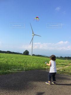 青空に凧をあげる幼女の写真・画像素材[1136944]