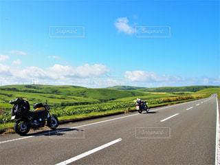 道の端にバイクに乗る人の写真・画像素材[1098473]