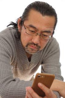 携帯電話を使用して眼鏡の男の写真・画像素材[1079868]
