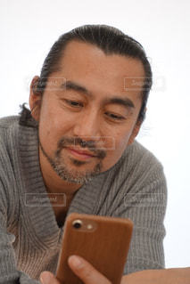 スマートフォンを見て微笑んでいる私の写真・画像素材[2316951]