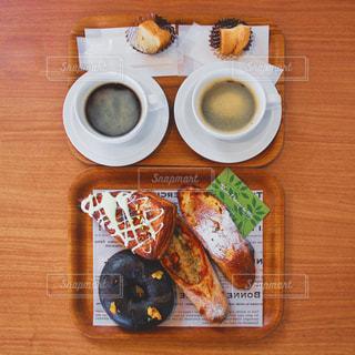 木のテーブルで食べるコーヒーとパンのランチ - No.1081431