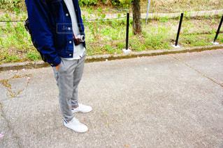 フェンスの横に立っている少年の写真・画像素材[1126103]
