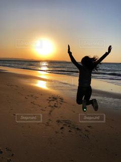 女性,海,空,屋外,砂,ビーチ,砂浜,ジャンプ,夕暮れ,波,海岸,夕方,景色,シルエット,人物,人,元気,夕陽,糸島,ポジティブ,フォトジェニック,カール,写真素材