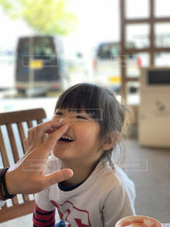 食べ物を食べながらテーブルに座っている女性の写真・画像素材[2345407]