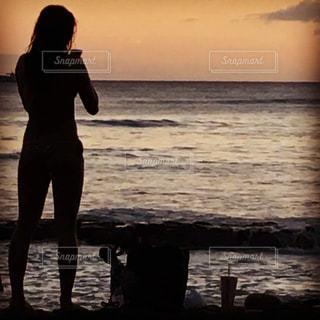 夕陽を撮影する女性の写真・画像素材[1411554]