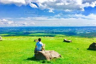 芝生のフィールドに座る人の写真・画像素材[1102202]