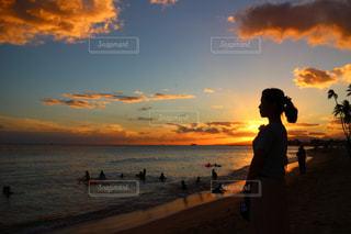 ビーチでの背景の夕日に人々 のカップルの写真・画像素材[1099922]