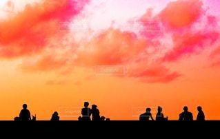 夕暮れ時に座っている人々 のグループの写真・画像素材[1268921]