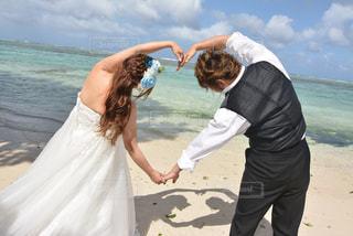 女性,男性,海,空,屋外,海外,雲,砂浜,結婚式,景色,ハート,人物,人,グアム,新郎,新婦,マーク,タキシード,ウエディングドレス