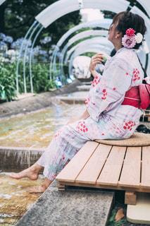 ベンチに座っている小さな女の子の写真・画像素材[2304745]