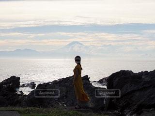 岩の多い浜辺に立つ男の写真・画像素材[2260759]
