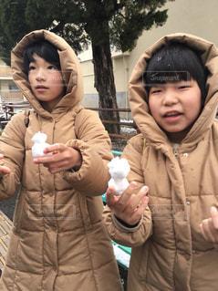雪の日の年子のダウンジャケットコーデの写真・画像素材[1748826]