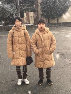 雪の日の年子のダウンジャケットコーデの写真・画像素材[1748827]