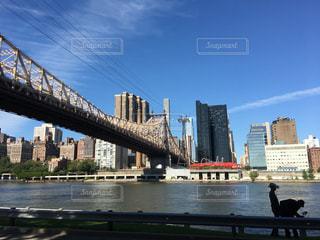 バック グラウンドで市と水の体の上の橋の写真・画像素材[1114606]