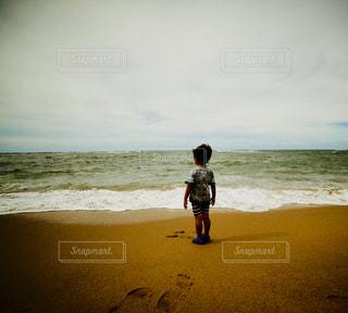 海の横にあるビーチの上を歩く男 - No.1217141