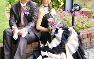 スーツと花の前に座ってネクタイを着ている人 - No.1227928