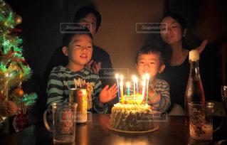 キャンドルとバースデー ケーキの前に座っている人の写真・画像素材[1667885]