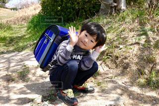 草の中に座っている小さな男の子の写真・画像素材[2811250]