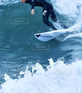 ウェットスーツを着た男が海の波の上でサーフィンをしているの写真・画像素材[3546978]
