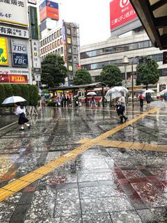 雨の中で傘を持って通りを歩いて人々 のグループの写真・画像素材[1247439]