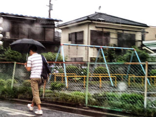 傘を持って通りを歩いている人の写真・画像素材[1247539]