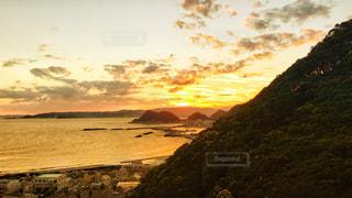 背景の山が付いている水の体に沈む夕日の写真・画像素材[1268780]