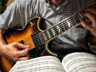 男性,室内,ギター,楽譜,楽器,音楽,クラシック,ジャズ,両手,曲,ストライプ柄,楽曲