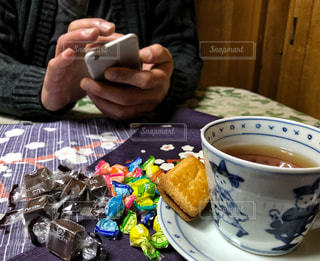 男性,室内,手,スマホ,テーブル,おやつ,お菓子,ティーカップ,チョコレート,セーター,紅茶,バレンタイン,2月