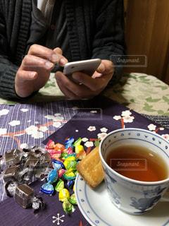 男性,冬,室内,手,スマホ,テーブル,お菓子,ティーカップ,チョコレート,セーター,紅茶,バレンタイン,ビスケット,無加工,2月