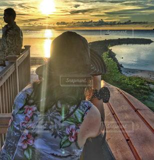 女性,海,カメラ,ロングヘア,ワンピース,島,夕焼け,ハイビスカス,帽子,日焼け,テラス,デッキ,撮影,旅行,海外旅行,花柄,フォトジェニック,肩,多色,パラオ共和国