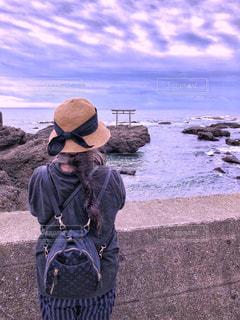 女性,ロングヘア,後ろ姿,帽子,鳥居,海岸,景色,旅行,お気に入り,ネイビー,紺色,フォトジェニック,Tシャツ,リュックサック,半袖,ストライプ柄