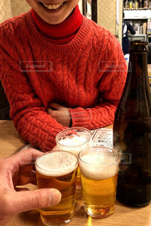 3人,赤,室内,手,テーブル,座る,笑顔,グラス,ビール,セーター,店内,乾杯,飲み会,ドリンク,瓶ビール,タートルネック,秋冬,とりあえず,3つ,着席,縄編み,乾杯フォト