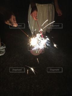ロウソクでケーキを切る人の写真・画像素材[1310433]