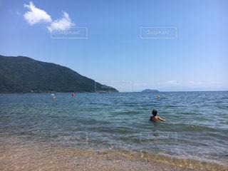 海の横にある水の体の横に立っている人の写真・画像素材[1391868]