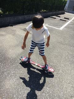 道路の側をスケート ボードに乗って少年の写真・画像素材[1394277]