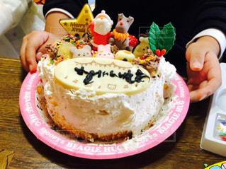 バースデー ケーキでテーブルに座っている女性の写真・画像素材[1696750]
