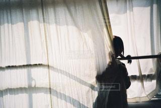 窓の前に立っている人の写真・画像素材[2172781]