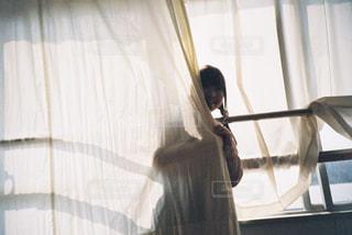 窓の前に立っている女性の写真・画像素材[2172783]