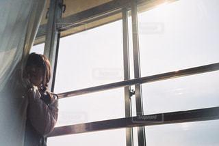 窓の前に立っている人の写真・画像素材[2172784]