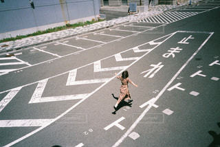 道路の脇にスケートボードに乗っている人の写真・画像素材[2439814]