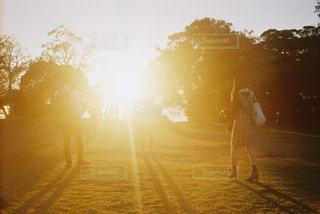 夕焼けの前に立つ人々のグループの写真・画像素材[2439914]