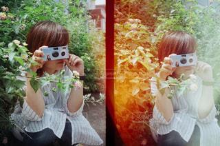 花瓶のあるテーブルに座っている少女の写真・画像素材[2439973]
