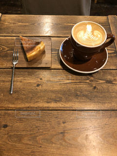木製のテーブルの上に座っているコーヒーのカップの写真・画像素材[2896007]