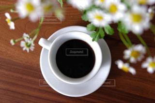 木製のテーブルの上に座っているコーヒーのカップの写真・画像素材[2896020]
