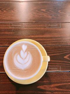 木製のテーブルの上に座っているコーヒーのカップの写真・画像素材[2896061]