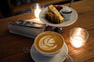 木製のテーブルの上に座っているコーヒーのカップの写真・画像素材[2911654]