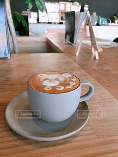 木製のテーブルの上に座っているコーヒーのカップの写真・画像素材[2934505]