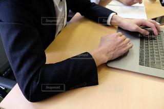机の上に座っているラップトップコンピュータを使用している人の写真・画像素材[2962989]