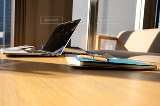 木製のテーブルの上に座っているラップトップコンピュータ付きの机の写真・画像素材[2962992]